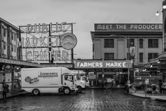 pikes place market delivery trucks in the rain black and white